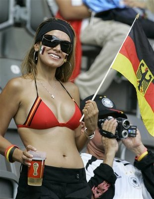 A hot German football supporter in a bikini drinking a beer.