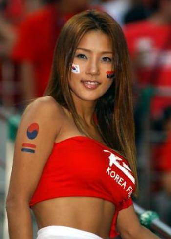 A hot South Korean football supporter smiling at the camera.