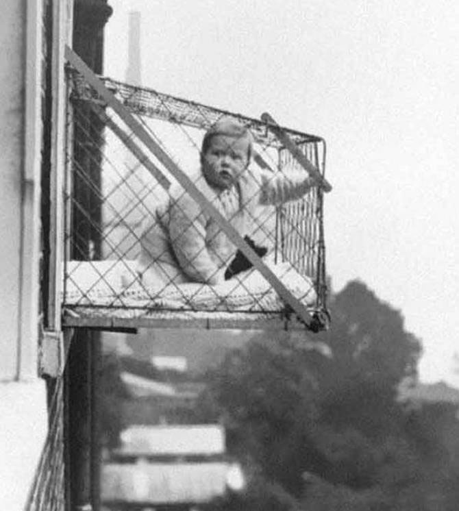 A Photo Of A Baby In A Cage Hanging Out An Apartment Window - 10 Eerie Photos That Will Send Shivers Down Your Spine