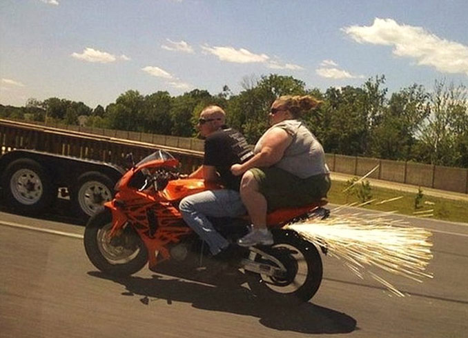 A man and a fat lady on a motorbike and the wheel is sparking - 20 WTF Photos You Just Have To See