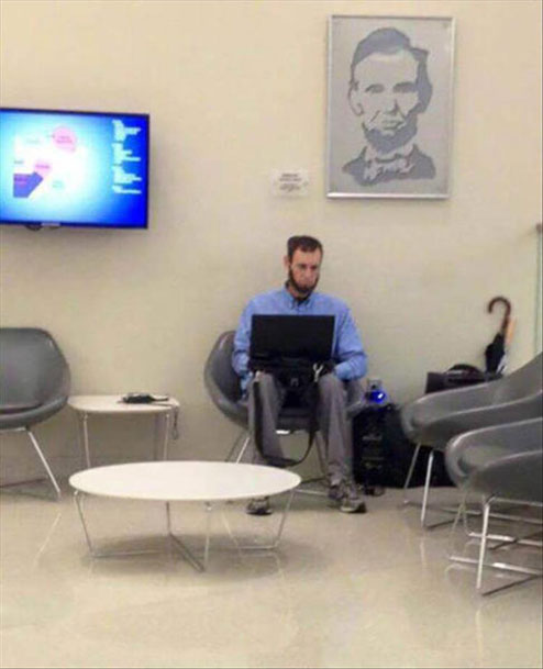 A man sitting in a waiting room that looks like the picture of Abraham Lincoln that is hanging on the wall.