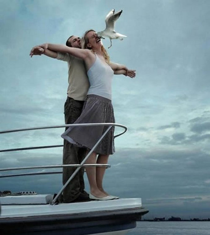 A couple standing at the front of a boat and a seagull has flown into the woman's face.