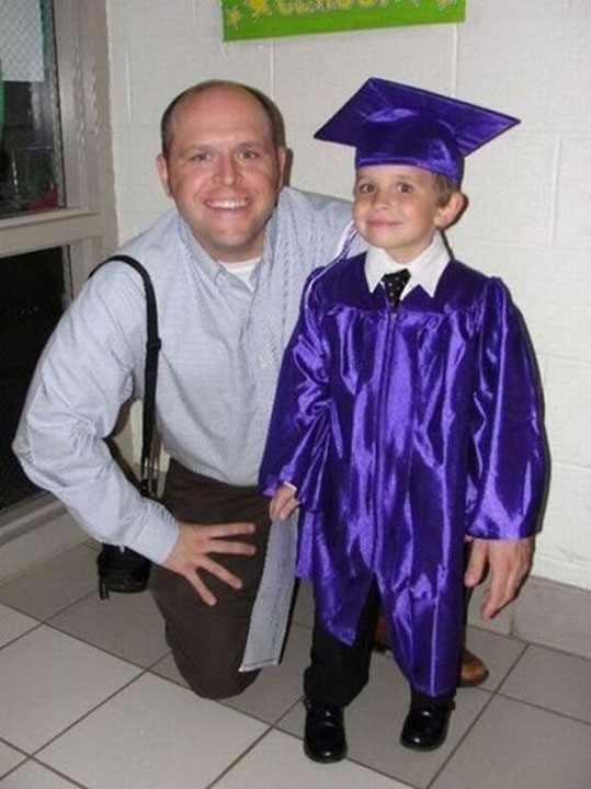 A boy dressed in a graduation robe that looks like he has a gigantic left hand.