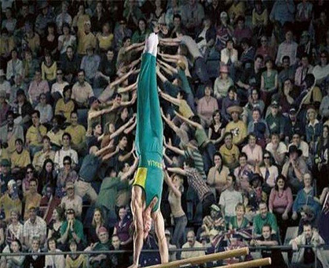 An Australian gymnast performing on the parallel bars that looks like he is being held in place by the crowd.