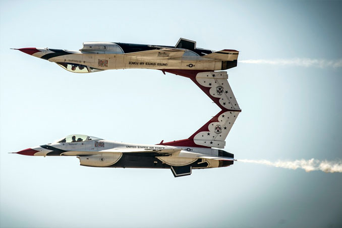 Two US AIr Force jets flying, one is upside down.