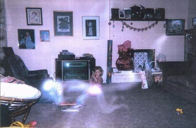 A mysterious photo of a young girl playing on the floor with a ghost in the foreground.