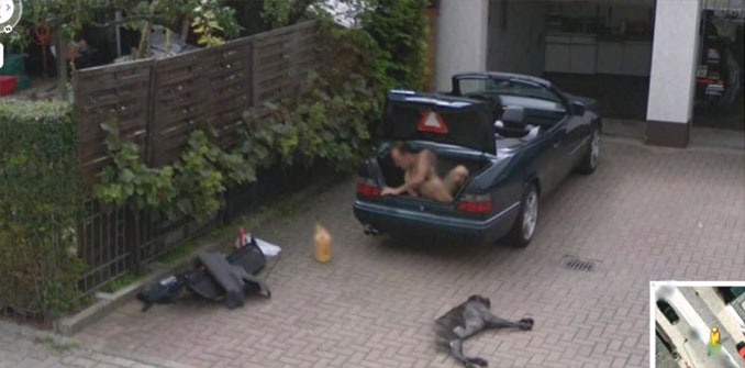 A man in the boot of his car with a dog lying on the driveway seen on Google Street View.