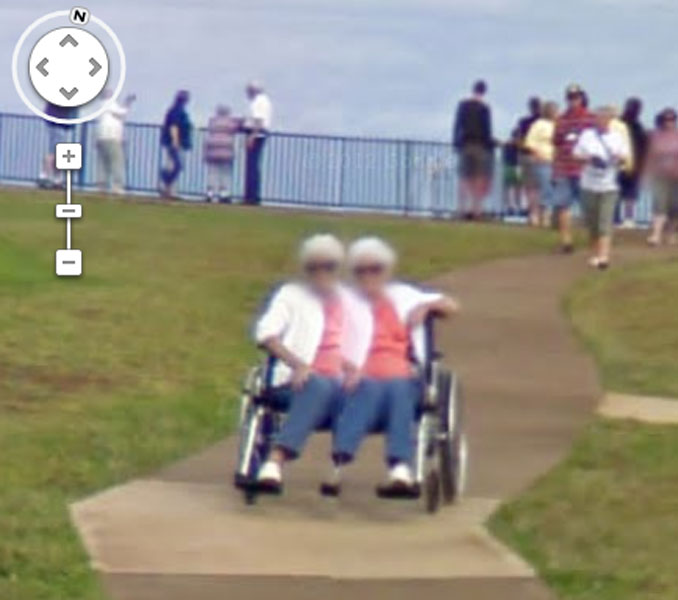 An old lady with two heads and three legs seen on Google Street View.