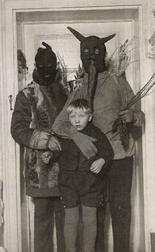 Two men dressed in devil costumes holding a young boy - The Scariest Halloween Costumes of All Time