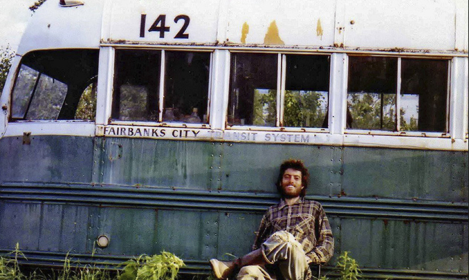 Chris McCandless sitting next to a bus - These Real Photos Have Very Disturbing Backstories
