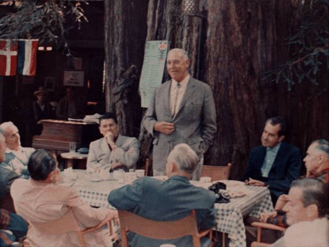 Richard Nixon and Ronald Reagan sitting at a table at the Bohemian Grove.