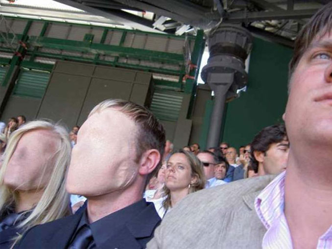 This is a scary picture of two faceless people sitting in a crowd. It can't be explained