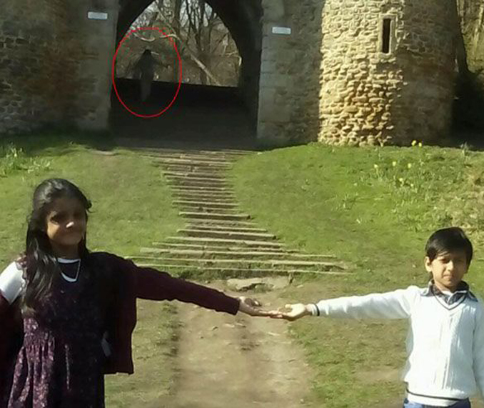 Two siblings holding hands in an old family photo that shows a ghost