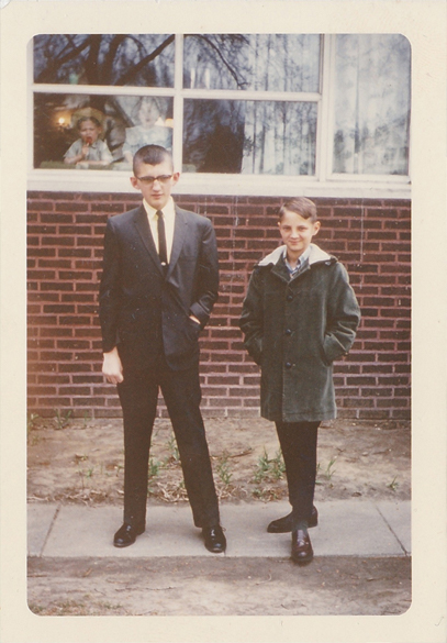 Two brothers standing next to each other in an old family photo, but is there a ghost in the window?