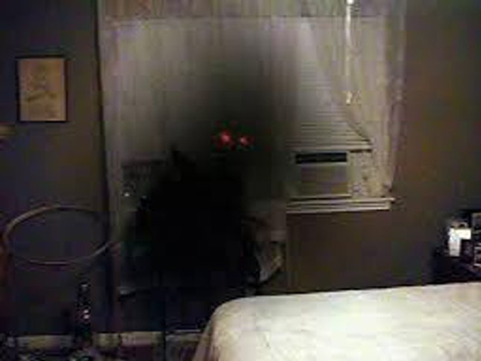 A red-eyed entity seen lurking in a room