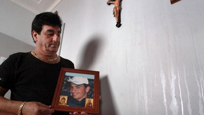 George Tannous holding a photo of his dead son, Mike, next to the miracle oil weeping from wall. Truly a paranormal mystery