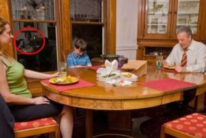 A family sitting at dinner table, possible ghost in background.