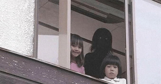 Two children stare out of a window with a scary shadow person behind them.