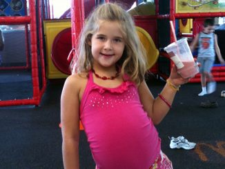 Photo of Annabel Beam holding milkshake at playground. Beam claims she's been to heaven.