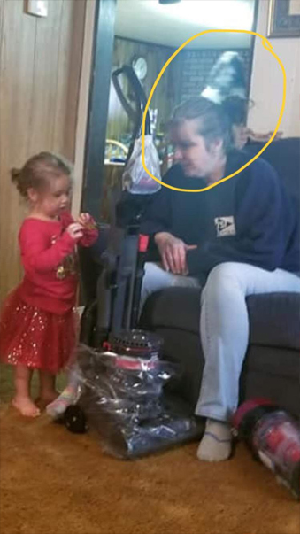 Ghost appears behind woman and young girl.