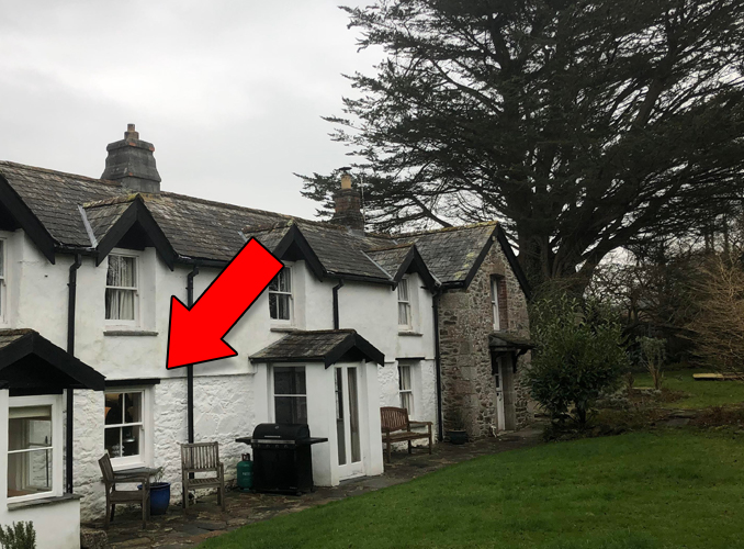 Photo of old house with mysterious cloaked figure in the window.