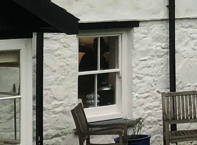 Close up photo of old house with mysterious cloaked figure in the window.