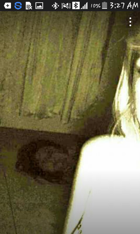 Brightened scary photo reveals ghostly head in the background.
